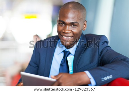 handsome african businessman using tablet computer at airport - stock photo