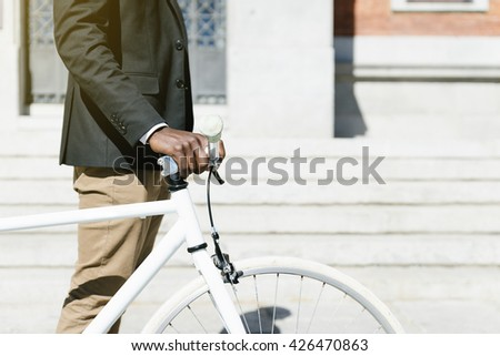 Handsome african man on bike in the city. Bicycle concept - stock photo