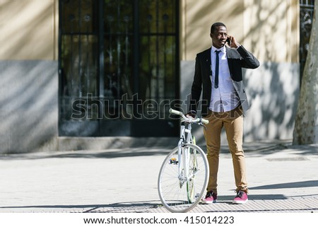 Handsome african man with mobile phone and fixed gear bicycle in the street. - stock photo