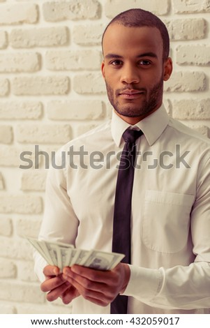 Handsome Afro American businessman in classic shirt and tie holding money, looking at camera and smiling, against white brick wall - stock photo