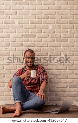 Handsome Afro American man in casual clothes and earphones is holding a cup of drink, listening to music and smiling, sitting against brick wall - stock photo