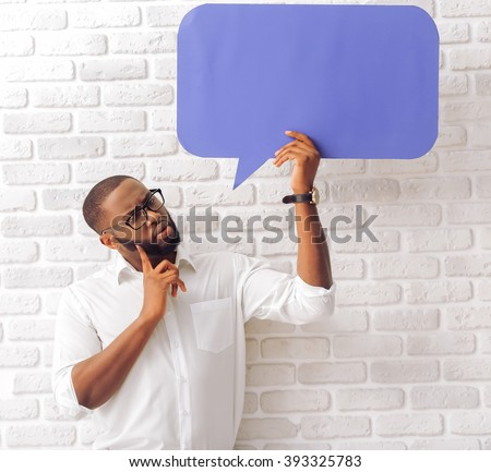 Handsome Afro American man in classic shirt and glasses is holding a speech bubble and thinking, standing against brick wall - stock photo