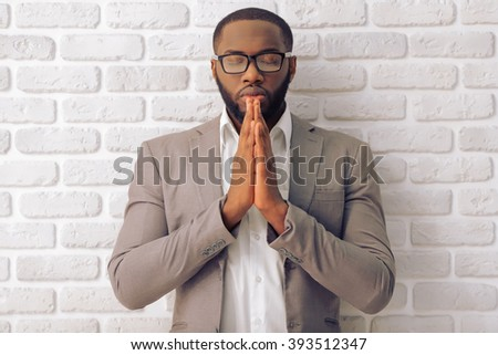 Handsome Afro American man in classic suit and glasses is keeping palms together like praying, standing against white brick wall - stock photo
