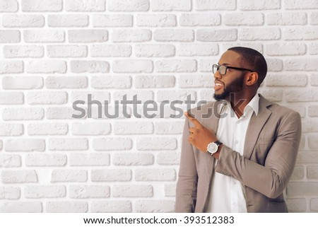 Handsome Afro American man in classic suit and glasses is smiling, looking and pointing away, against white brick wall - stock photo