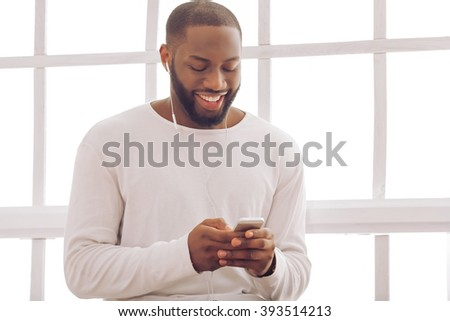 Handsome Afro American man is listening to music using a smart phone and smiling while sitting near the window at home - stock photo
