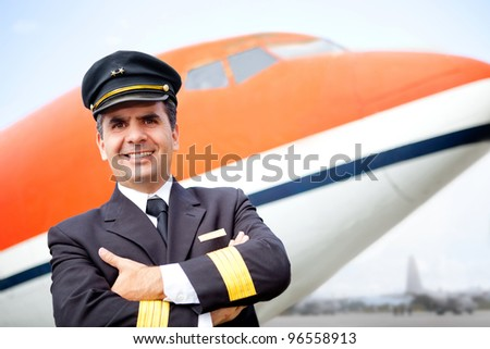 Handsome airplane pilot smiling at the airport - stock photo