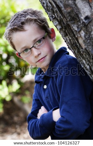 handsome and confident young boy in glasses leans against a tree with arms folded across his chest - stock photo