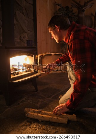 handsome and rugged man stoking wood stove fire - stock photo