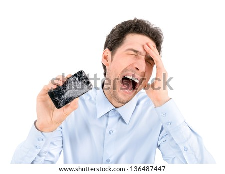 Handsome angry businessman showing broken smartphone with crashed screen. Isolated on white background. - stock photo