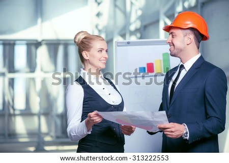 Handsome architect is discussing the ideas of building with his colleague. They are holding a blueprint and looking at each other with joy. The workers are standing near a whiteboard and smiling - stock photo