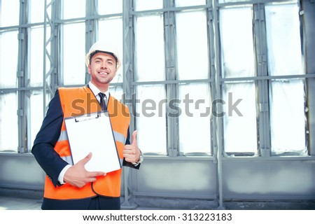 Handsome architect is standing and holding a folder of documents. He is showing paper to the camera and smiling. The man is giving thumb up happily. Copy space in right side - stock photo