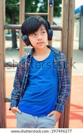Handsome Asian boy listening to music on headphones - stock photo