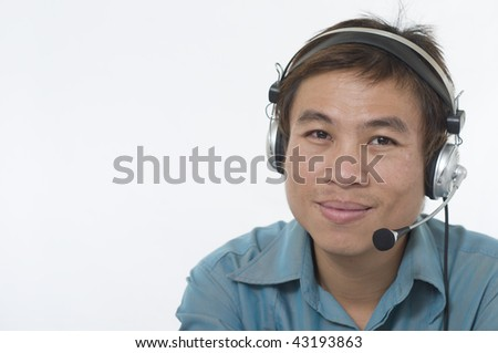 Handsome Asian business man wearing headset and smiling - stock photo