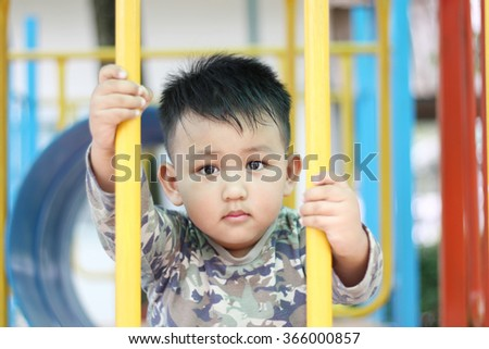 Handsome asian kid having fun playing play house at outdoor playground on a bright sunny day. Little boy in green soldier shirt. Children's hand holding an iron grating player. - stock photo