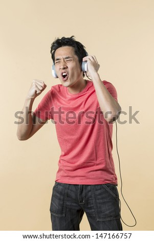 Handsome Asian man wearing earphones singing and dancing to music. standing against cream background. - stock photo