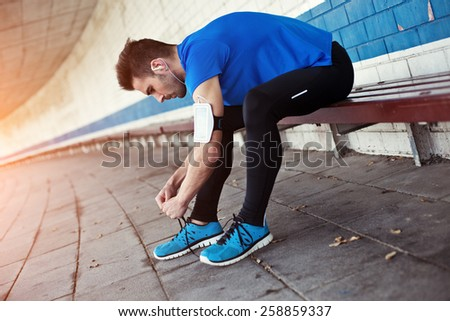handsome athlete tying shoelaces and preparing for running (intentional sun glare) - stock photo
