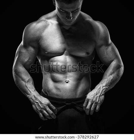 Handsome athletic guy prepare to do exercises. Isolated image, black background. - stock photo