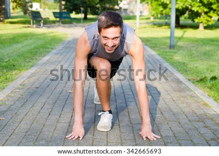 Handsome Athletic Man in Running Start Position - stock photo