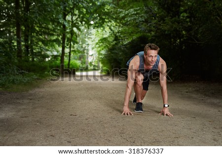 Handsome Athletic Man in Running Start Position and Looking Into the Distance at the Park - stock photo
