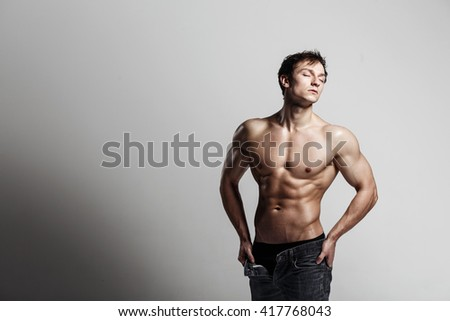 Handsome athletic man looking at side in unbuttoned jeans. Strong bodybuilder with six pack, perfect abs, shoulders, biceps, triceps and chest. Great fitness body. Ideal for commercial.Gray background - stock photo