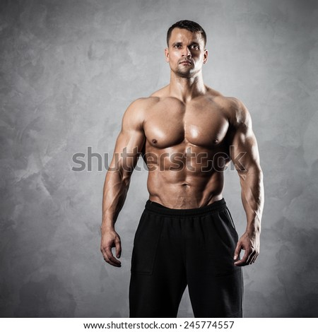 Handsome athletic man posing on gray background - stock photo