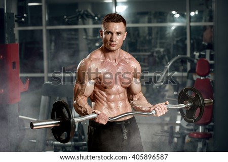 Handsome athletic man power training with dumbbells pumping muscle - stock photo