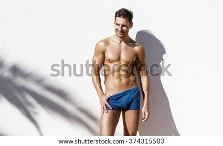 Handsome athletic man wearing swimming trunks - stock photo