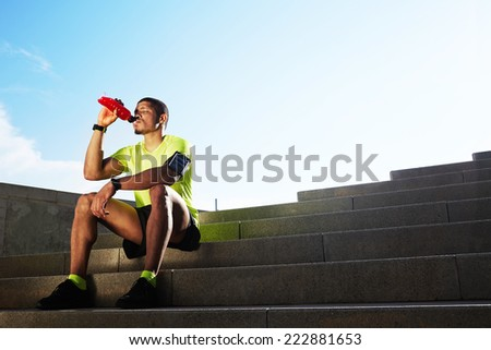 Handsome athletic runner seated on the steps drink water, beautiful fit man in bright fluorescent sportswear, sports fitness concept - stock photo