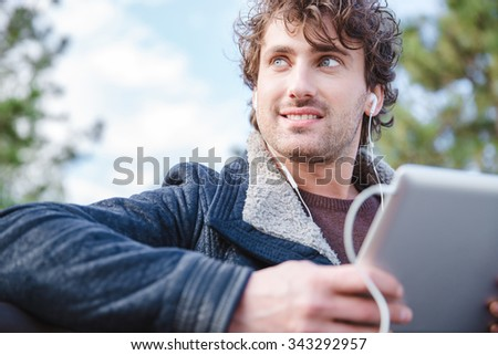 Handsome attractive smiling happy joyful young male in black jacket using tablet and looking away - stock photo