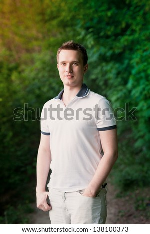 Handsome attractive young man standing in the park outdoor - stock photo