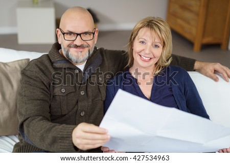 Handsome bald man and his wife seated on couch and smiling at the camera while holding paperwork - stock photo