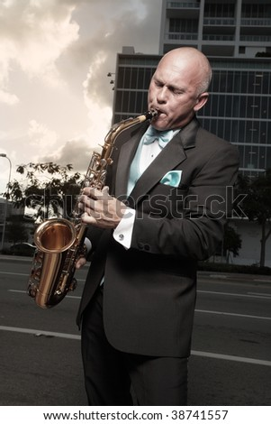 Handsome bald man playing a saxophone - stock photo