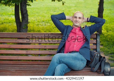 handsome bald man sitting on a bench in the park - stock photo