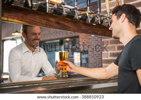 Handsome bar tender giving a pint for a customer in a pub - stock photo