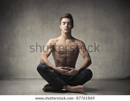 Handsome bare-chested man doing yoga - stock photo
