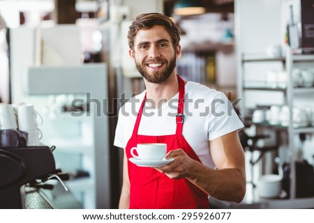 Handsome barista holding a cup of coffee at the cafe - stock photo