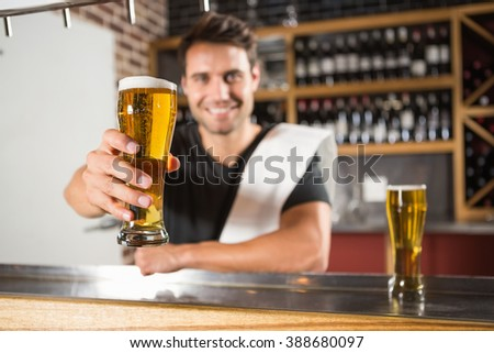 Handsome barman holding a pint of beer in a pub - stock photo