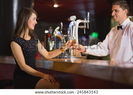 Handsome barman serving champagne to customer in a bar - stock photo