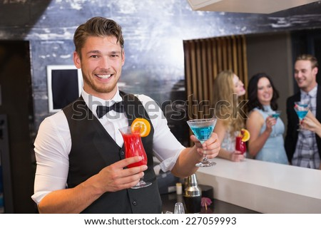 Handsome barman smiling at camera holding cocktails at the bar - stock photo