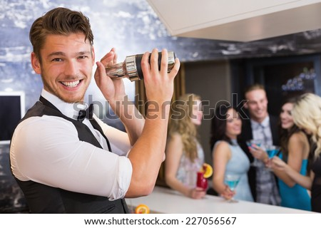 Handsome barman smiling at camera making a cocktail at the bar - stock photo