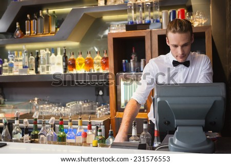 Handsome barman standing at the cash register in a bar - stock photo