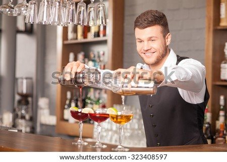 Handsome bartender is creating cocktails in bar. He is holding two shakers. The man is pouring beverage from it into three glasses. He is standing and smiling - stock photo