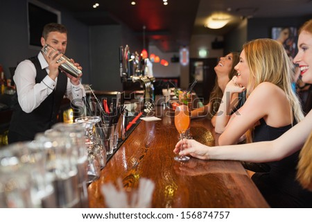 Handsome bartender making cocktails for beautiful women in a classy bar - stock photo