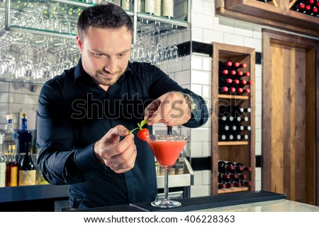 Handsome bartender mixologist decorating strawberry martini style cocktail in bar black shirt stylish  - stock photo