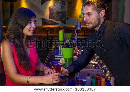 handsome bartender seduces a beautiful woman - stock photo