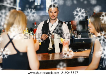 Handsome bartender working while gorgeous friends speaking against snowflakes - stock photo