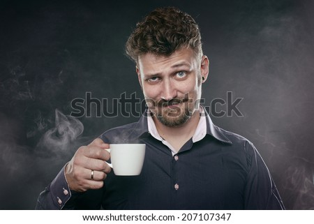 handsome beard man stand in fog with cup of coffee in his hand and look at camera - stock photo