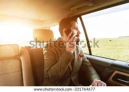 handsome bearded businessman sitting on back seat of car and talking on phone - stock photo