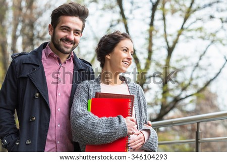 Handsome bearded man walking onthe street with hisgirl-friend who is holding documents and files during autumn weather. - stock photo