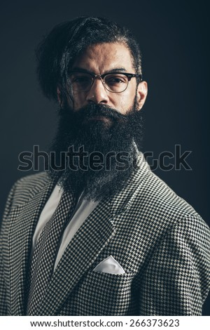 Handsome bearded man wearing glasses and a checked suit and tie looking grimly at the camera on a dark shadowed background - stock photo